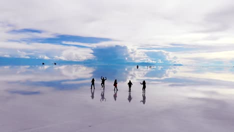 Aerial-of-silhouetted-people-dancing-on-the-Uyuni-salt-flats-lake-with-perfect-reflections-in-Bolivia