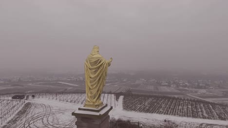 Aerial-of-golden-statue-of-Jesus-Christ-with-outstretched-arms-in-Fatima-Portugal-in-snowy-winter-weather