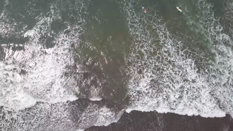 Aerial-shot-looking-straight-down-at-surfers-in-waves-