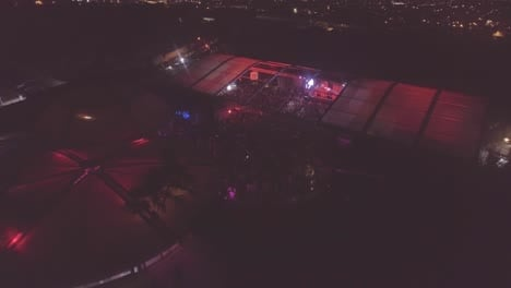 Slow-descent-aerial-over-a-massive-indoor-outdoor-rock-concert-or-dance-club-at-night-with-huge-crowds