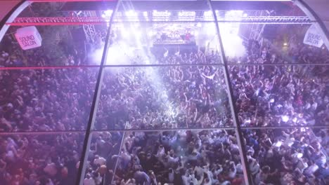 Aerial-over-a-massive-indoor-outdoor-rock-concert-or-dance-club-at-night-with-huge-crowds-partying-and-dancing