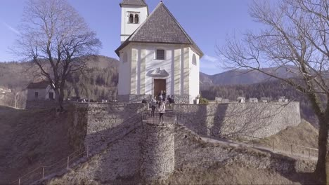 Aerial-of-a-small-white-church-in-the-mountains-of-Slovenia-and-woman-and-photographers
