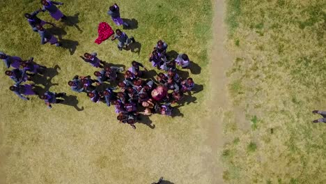 Rising-straight-down-drone-aerial-of-African-children-laughing-and-waving-at-a-school-or-orphanage-in-Kenya