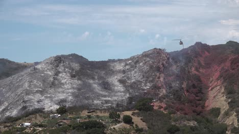 Helicopter-Water-Drop-And-Firefighters-Mop-Up-After-A-Brush-Fire-Burns-A-Hillside-Near-Hollister-Ranch-In-Santa-Barbara-California