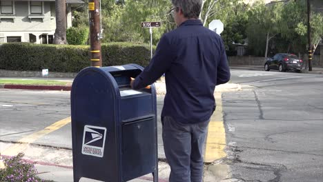 A-Man-Walks-To-A-Mailbox-And-Mails-A-Homemade-Voter-Registration-Card-Encouraging-People-To-Vote-In-The-Election