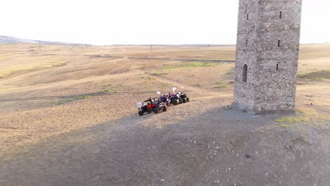 Aerial-Over-Atsvs-And-Riders-Parked-Near-A-Stone-Monument-In-The-Republic-Of-Georgia