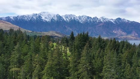 Aerial-Shot-Over-Trees-Reveals-Queenstown-New-Zealand-And-Remarkables-Mountain-Range