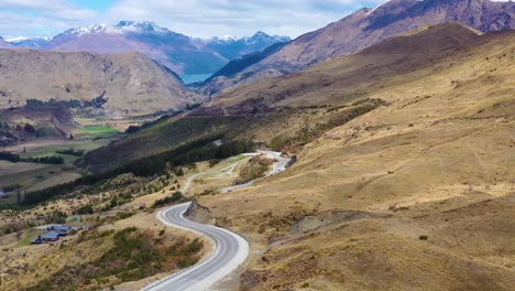 Aerial-Shot-Over-A-Road-In-The-South-Island-Of-New-Zealand-Reveals-Queenstown-And-Remarkables-Mountain-Range-Distant