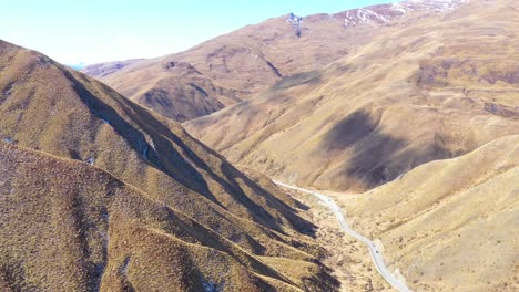 Aerial-Over-Cars-Traveling-On-A-Road-Through-Dry-Mountain-Landscape-In-The-South-Island-Of-New-Zealand