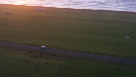 Vista-Aérea-Over-A-Car-Driving-Along-A-Lake-Or-Shoreline-In-The-South-Island-Of-New-Zealand