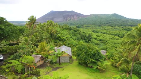 Very-Good-Aerial-Over-A-Jungle-Village-On-The-Island-Of-Tanna-Reveals-Mt-Yasur-Volcano-In-The-Distance-Vanuatu