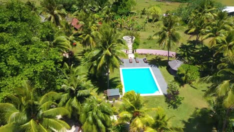 Aerial-Pull-Back-From-A-Young-Tourist-Woman-Beside-A-Hotel-Pool-At-A-Tourist-Resort-On-Vanuatu-Pacific-Islands