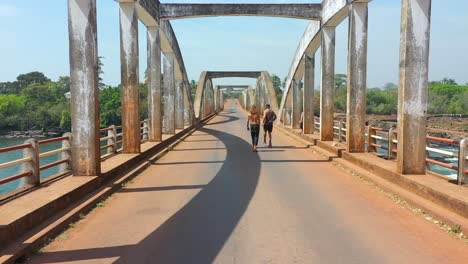 Pov-Shot-Of-Two-Men-Skateboarding-Over-The-Corumbal-River-In-Guineabissau-West-Africa