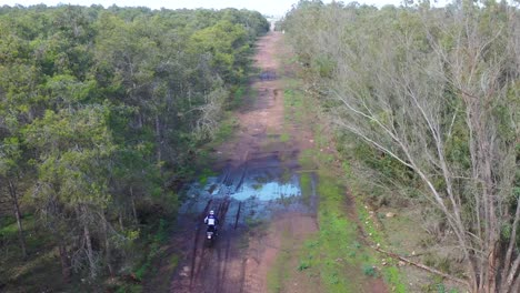 A-Dirt-Bike-Motorcycle-Rider-Drives-On-A-Backroad-Area-With-Some-Large-Water-Puddles-1