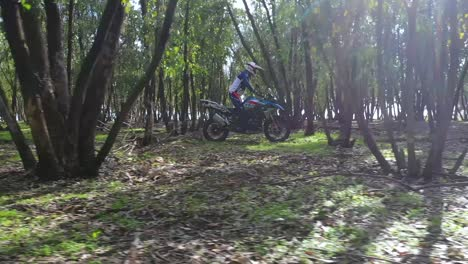 A-Dirt-Bike-Motorcycle-Rider-Drives-Through-A-Forest-Area-1