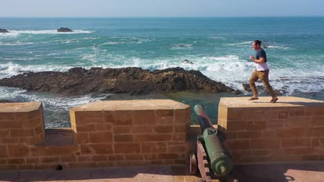A-Man-Runs-Along-The-Ramparts-And-Jumps-Over-Cannons-In-The-Ancient-City-Of-Essaouira-Morocco