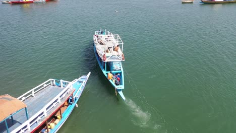 Aerial-Over-A-Wooden-Tourist-Boat-Leaving-A-Small-Harbor-And-Heading-Up-The-Gambie-River-Near-Banjul-Gambia
