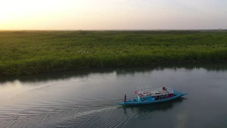 Beautiful-Aerial-Over-Small-Boat-Moving-Along-The-Gambia-River-In-West-Africa-Through-Mangrove-Forests-And-Winding-Bends