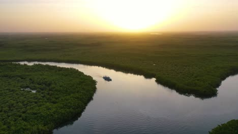 Beautiful-Aerial-Over-Small-Boat-Moving-Along-The-Gambia-River-In-West-Africa-Through-Mangrove-Forests-And-Winding-Bends-3