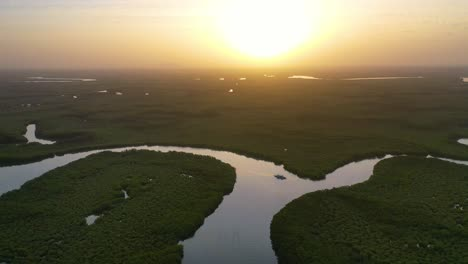 Beautiful-Aerial-Over-Small-Boat-Moving-Along-The-Gambia-River-In-West-Africa-Through-Mangrove-Forests-And-Winding-Bends-4