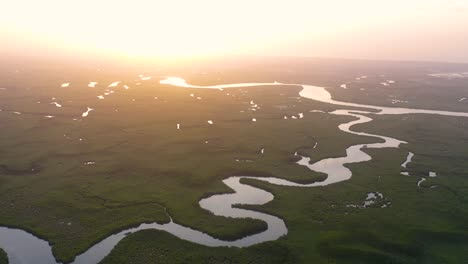 Beautiful-Aerial-Over-Small-Boat-Moving-Along-The-Gambia-River-In-West-Africa-Through-Mangrove-Forests-And-Winding-Bends-5