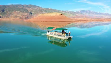 Pov-Vista-Aérea-Of-A-Man-Jumping-Off-A-Tourist-Boat-Soaked-In-Champagne-On-Lake-Bin-El-Ouidane-Morocco