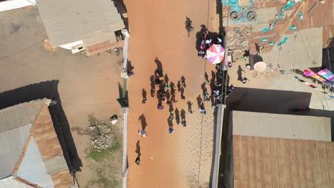 Los-Niños-Saludan-Mientras-Un-Dron-Despega-Sobre-Ellos-En-Un-Camino-De-Tierra-En-África-Occidental