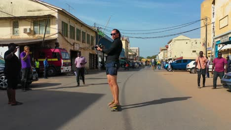 A-Tourist-Skates-Down-A-Street-In-Gambia-West-Africa-On-A-Skateboard