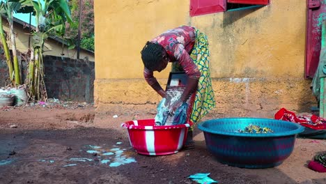 A-Woman-Washes-Clothes-By-Hand-Using-A-Washboard-In-West-Africa