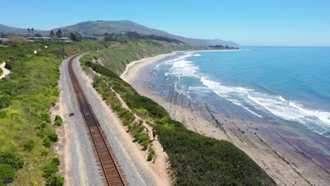 Aerial-Over-Man-Walking-On-Railroad-Tracks-Above-The-Pacific-Coast-Near-Carpinteria-Bluffs-Santa-Barbara-California