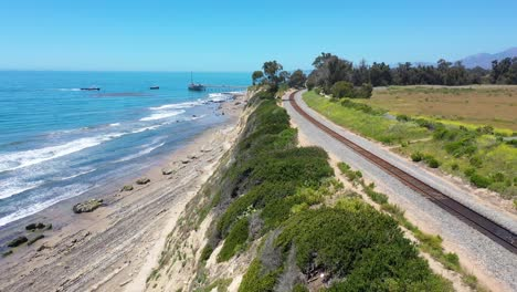 Aerial-Over-Railroad-Tracks-Above-The-Pacific-Coast-Near-Carpinteria-Bluffs-Santa-Barbara-California