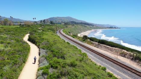 Antenne-Eines-Mannes-Der-Sein-Fahrrad-Mit-Den-Bergen-Von-Santa-Barbara-Im-Hintergrund-In-Der-Nähe-Von-Carpinteria-California-2-Fährt