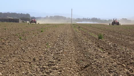 Farm-Tractors-Move-Across-Dry-Dusty-Landscape-In-California-Suggesting-Drought-And-Climate-Change