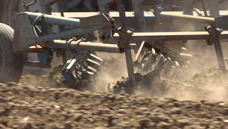 Tractor-Plow-Blades-Move-Through-Dry-Dusty-Earth-In-California-Suggesting-Drought-And-Climate-Change