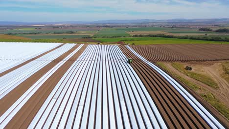 Aerial-Of-Tractors-Laying-Rows-Of-Plastic-Covering-On-Farm-Fields-Near-Santa-Maria-California-1