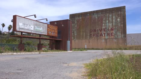 Establishing-Shot-Of-An-Abandoned-Drive-In-Movie-Theater-With-Man-On-Harley-Motorcyle-Passing