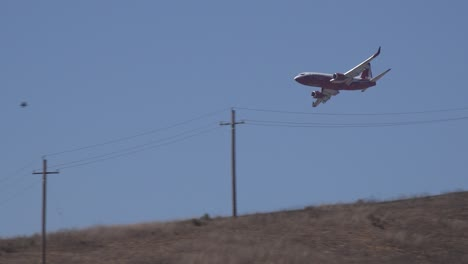 Fixed-Wing-Aircraft-Drops-Fire-Retardant-Phos-Chek-On-A-Brush-Fire-Burning-In-The-Hills-Of-Southern-California-Looks-Like-A-Plane-Crash-Behind-Hillside-1