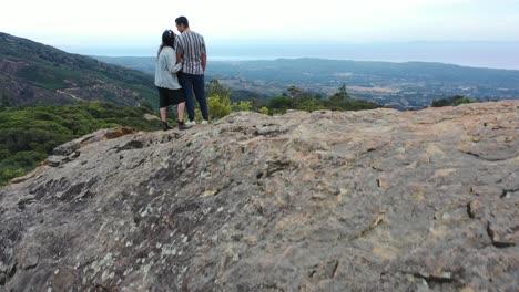 Aerial-Man-And-Woman-Climb-A-Rock-And-Take-Selfie-Photos-Overlooking-Santa-Barbara-California