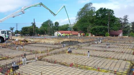 Antena-Notable-Sobre-El-Sitio-De-Construcción-Con-Grúas-Gigantes-Y-Trabajadores-Vertiendo-Cimientos-De-Hormigón-En-Ventura-California