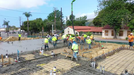 Construction-Workers-At-Construction-Site-With-Giant-Crane-Pouring-Concrete-Foundation-In-Ventura-California