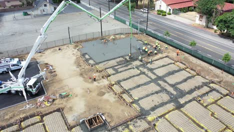 Remarkable-Aerial-Over-Construction-Site-With-Giant-Crane-And-Workers-Pouring-Concrete-Foundation-In-Ventura-California-1