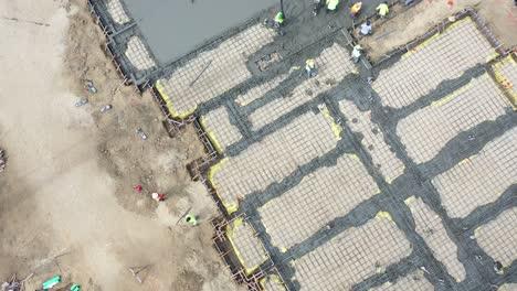 Antena-De-Arriba-Hacia-Abajo-Sobre-El-Sitio-De-Construcción-Con-Grúas-Gigantes-Y-Trabajadores-Vertiendo-Cimientos-De-Hormigón-En-Ventura-California