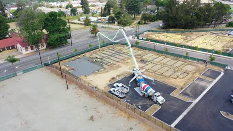 Remarkable-Aerial-Over-Construction-Site-With-Giant-Crane-And-Workers-Pouring-Concrete-Foundation-In-Ventura-California-2