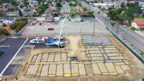 Remarkable-Aerial-Over-Construction-Site-With-Giant-Crane-And-Workers-Pouring-Concrete-Foundation-In-Ventura-California-3