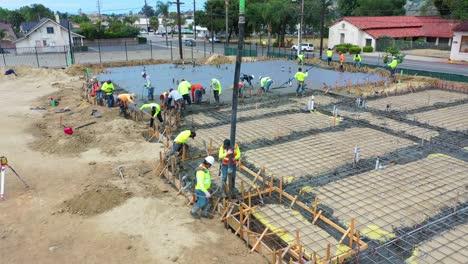 Ziehen-Sie-Die-Antenne-Von-Bauarbeitern-Auf-Der-Baustelle-Mit-Einem-Riesigen-Kran-Zurück-Der-Ein-Betonfundament-In-Ventura-Kalifornien-Gießt