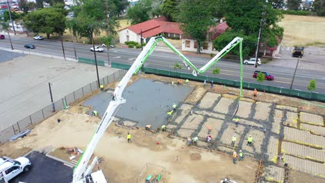 Remarkable-Aerial-Over-Construction-Site-With-Giant-Crane-And-Workers-Pouring-Concrete-Foundation-In-Ventura-California-4