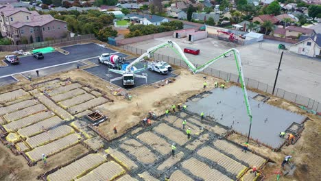 Remarkable-Aerial-Over-Construction-Site-With-Giant-Crane-And-Workers-Pouring-Concrete-Foundation-In-Ventura-California-5