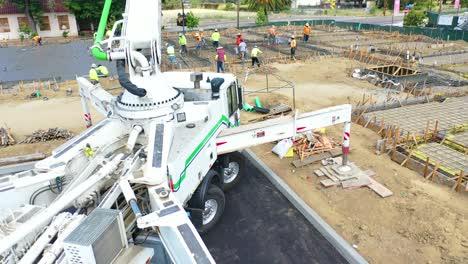 Steigende-Antenne-über-Baustelle-Mit-Riesigem-Kran-Und-Arbeitern-Die-Betonfundament-In-Ventura-Kalifornien-Gießen-