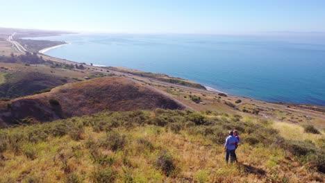 Vista-Aérea-Retired-Couple-Standing-At-Mountaintop-Overlook-Ocean-Or-Coastline-On-A-Ranch-Near-Santa-Barbara-California