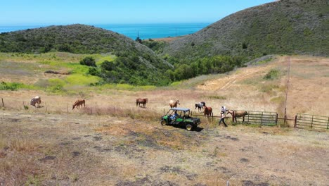 Aerial-Of-Ranchers-Visiting-With-Horses-Grazing-On-A-Ranch-Or-Farm-With-Ocean-Background-Near-Santa-Barbara-California